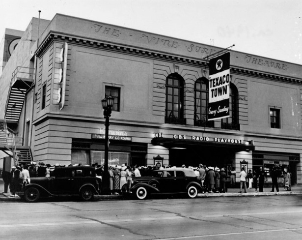 "The CBS Radio Playhouse (originally Vine Street Theater) during a broadcast of ""Texaco Town,"" c. 1937. Frank Kerwin's Merry-Go-Round can be seen on the ground floor."